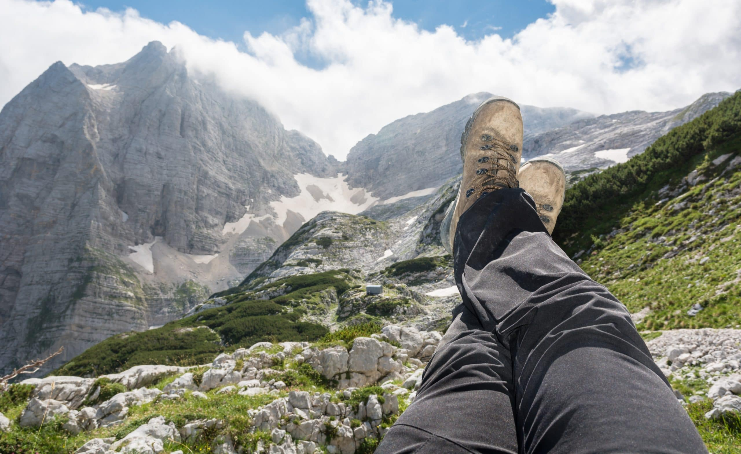 Pair of leggs stretched into the air with a mountain view